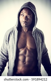 Handsome shirtless muscular black young man with jacket open on naked torso, looking at camera, on light background in studio shot