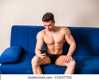 Handsome shirtless muscular bodybuilder man typing or surfing the internet with cell phone while sitting on couch