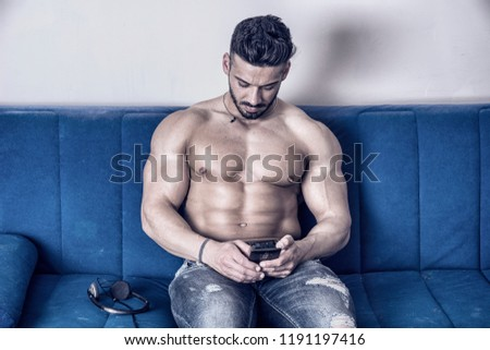Handsome shirtless muscular bodybuilder man typing or surfing the internet with cell phone while laying on couch