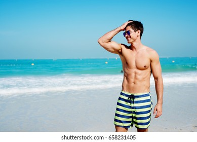 Handsome shirtless muscular fitness man at the beach, looking aside and smiling.