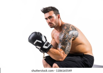 Handsome shirtless and muscular man with boxer's gloves in studio shot