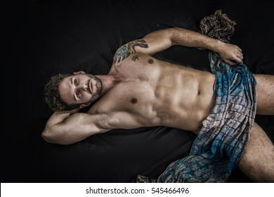 Handsome shirtless muscular man in briefs, covering with long elegant scarf, lying on the floor, on dark background in studio shot