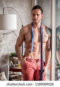 Handsome shirtless muscular man at home standing and looking away