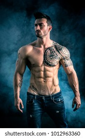 f9055603e fashion tattoo man. Handsome shirtless muscular man with jeans, standing,  on dark smoky background in studio shot
