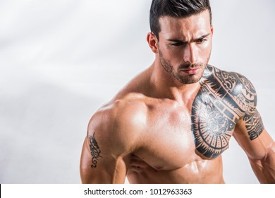 Handsome shirtless muscular man with jeans, standing, on white background in studio shot