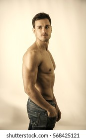 Handsome shirtless muscular man's profile, looking away, on light background in studio shot