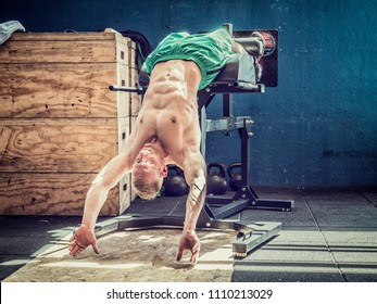 Handsome shirtless muscular young man athlete exercising abs with equipment in gym, hanging upside down