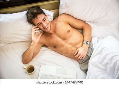 Handsome shirtless muscular young man in bed talking on cell phone placing a call