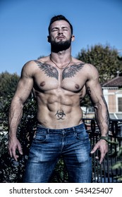 Handsome shirtless muscular young man outdoor on a balcony or terrace, wearing only jeans, looking away