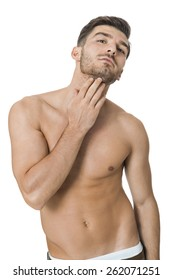 Handsome shirtless naked bearded young man standing looking intently at the camera with his hand to his chin in a sensual sexy pose, isolated on white