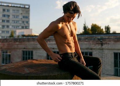 Handsome shirtless, sexy brunette young man with tanned athletic body, seated in profile on old roof at the sunset.