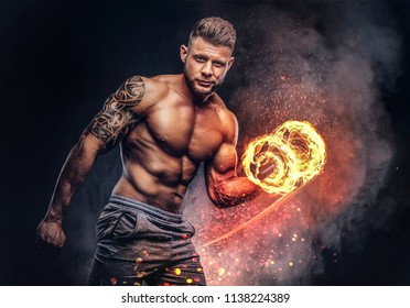 88582b58d Handsome shirtless tattooed bodybuilder with stylish haircut and beard,  wearing sports shorts, posing in