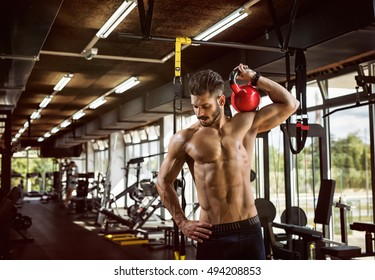 Handsome shirtless weightlifter working out at the gym with kettlebell.