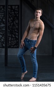 Handsome shirtless young male model with naked feet in blue jeans at modern interior photostudio