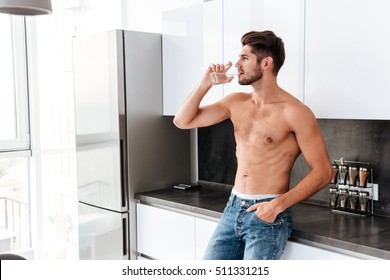 Handsome shirtless young man drinking waten on the kitchen