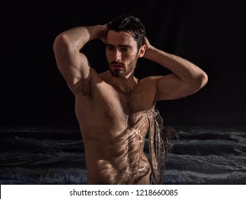 Handsome shirtless young man outdoor at night bathing in sea or ocean, with ripped fit body