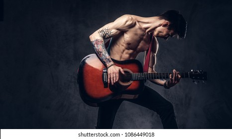 Handsome shirtless young musician playing guitar while jumping.