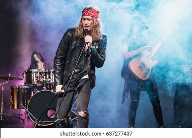 Handsome singer with rock and roll band performing music on stage