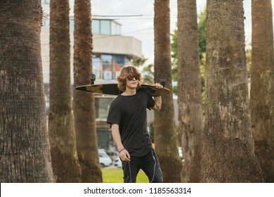 Handsome skateboarder wering sunglasses holds longboard on shoulder on city street or tropic background