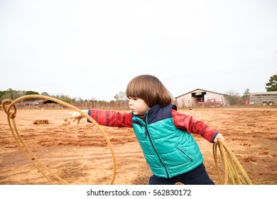 Handsome small toddler boy training making loope and throwing lasso in ranch. Red clay background, rural. Country lifestyle