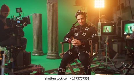 Handsome Smiling Actor Wearing Motion Capture Suit and Head Rig having Lunch Break, Sitting on Chair, Looking at Camera. Studio High Budget Movie. On Film Studio Period Costume Drama Film Set