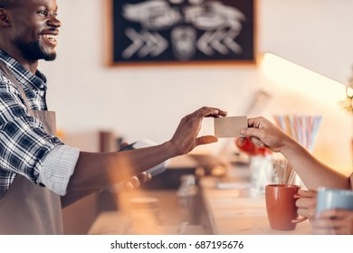 handsome smiling african american barista taking credit card for payment on bar counter in cafe