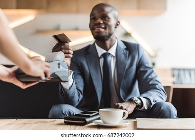 handsome smiling african american businessman paying with credit card in cafe