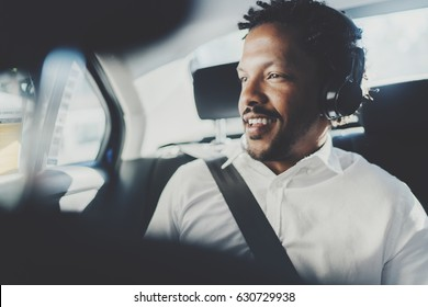 Handsome smiling african man listening music on smartphone while sitting on backseat in taxi car.Concept of happy young people traveling in the city.Blurred background