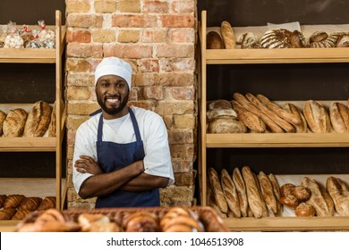 handsome smiling baker with folded arms standing at pastry store