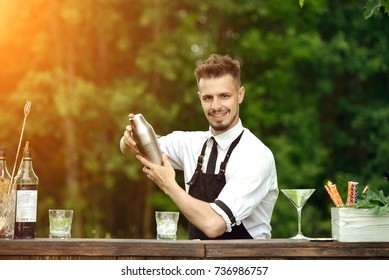 Handsome smiling barman shaking and mixing cocktail outdoors, catering bar service. Concept of preparation cocktail and small business