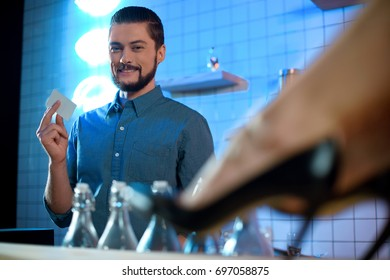 handsome smiling bartender holding blank card and female legs in high heeled shoes on foreground