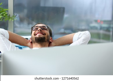 Handsome smiling bearded adult clerk person arms crossed up over head sit behind laptop pc display at office workplace desk portrait. Stress free home worker people optimistic cozy carefree pleasure