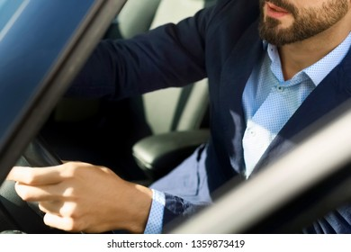 Handsome smiling bearded man in car