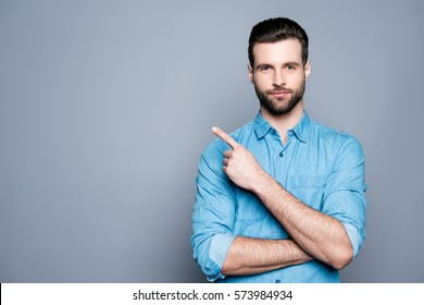 Handsome smiling bearded man pointing away on gray background.