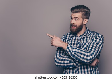 Handsome smiling bearded man showing direction with finger