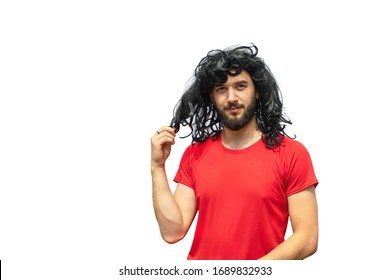Handsome smiling bearded man in wig of curly long messy hair and red t-shirt isolated on white. Copy space. Exotic hair-do. Time to visit barbershop