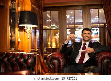 Handsome smiling brunette sitting with a cup of coffee in a luxury interior