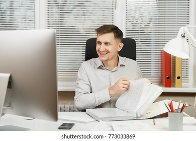 Handsome smiling business man in shirt sitting at the desk, working at computer, black folder, documents in light office, looking to contemporary monitor, on window background. Manager or worker