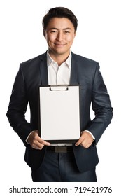 Handsome smiling businessman in a blue suit and white shirt, holding a clipboard with a blank paper. Standing in front of a white background.