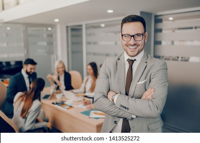 Handsome smiling businessman in formal wear and eyeglasses standing at boardroom with arms crossed. Love and respect do not automatically accompany a position of leadership. They must be earned