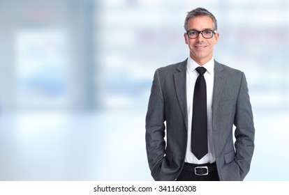 Handsome smiling businessman over blue banner background.