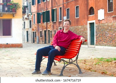 Handsome smiling Caucasian male wearing red dress shirt in early fifties sitting on red painted bench in empty town square of old Italian town in Venice, italy