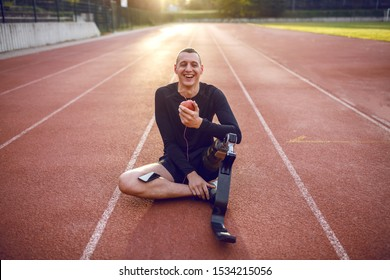 Handsome smiling caucasian sporty handicapped young man in sportswear and with artificial leg sitting on racetrack, listening music and eating apple.
