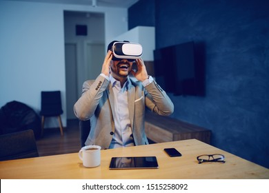 Handsome smiling Caucasian unshaven man in suit sitting in dining room in morning and using virtual reality headset. On table are eyeglasses, smart phone, tablet and coffee.