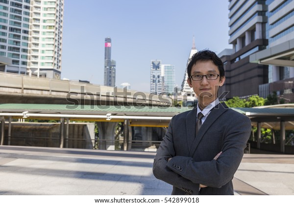 Handsome smiling confident businessman portrait,Portrait of a handsome CEO smiling,young asian businessman portrait on city background