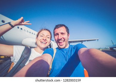 handsome smiling couple tourist ready for boarding on plane in airport, summer vacation and travel around the world, view of airplane in background