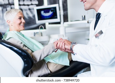 Handsome smiling dentist looking at x-ray image of his senior woman patient.