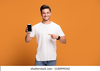 Handsome smiling excited man showing mobile phone posing on yellow studio background.