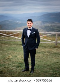 Handsome smiling goom poses in his perfect black suit outside on mountain hill