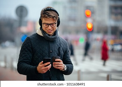 Handsome smiling guy in eyeglasses listening to music in headphones, using his mobile phone, holds cup of coffee, standing on the street. Dressed in warm jacket.